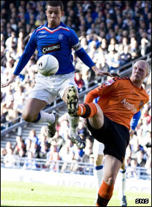Garry Kenneth challenges the Rangers captain Barry Ferguson for the ball
