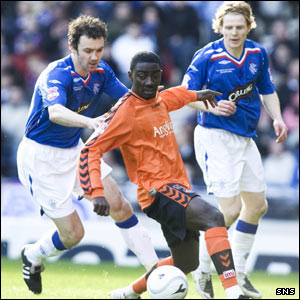 Dundee United's Prince Buaben shrugs off a challenge from Christian Dailly
