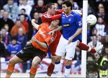The Rangers keeper Allan McGregor fends off a challenge from Lee Wilkie as United come close to adding a second goal