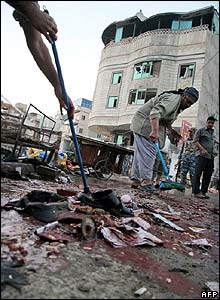 People mop up blood at the site of the Karbala attack