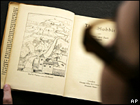 A Bonhams auctioneer reading the first edition of The Hobbit