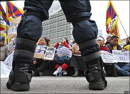 A riot policeman stands in front of Tibetan protesters at EU headquarters in Brussels on Tuesday
