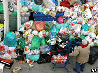 An elderly man looks at a pile of uncollected rubbish caused by a municipal workers' strike in Athens, 18 March, 2008