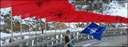 An ethnic Kosovo Albanian boy carries a Nato flag on a bridge decorated with Albanian flags near the town of Kacanik, Kosovo