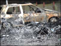 Burnt car and barbed wire following Monday's riots in Mitrovica