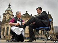 The Bishop of Birmingham, Rt. Revd David Urquhart, polishes shoes