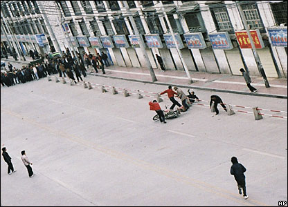Tibetan protesters attack a Chinese motorcyclist as a crowd looks on, 14/03/08