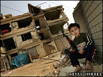 A young Iraqi refugee holds a toy rifle outside a bombed-out building in Baghdad (19 March 2008)