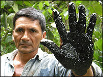 Achuar Leandro Rengifo shows oil on hand, Peru
