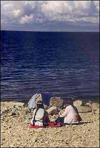 Women sit on the shores of Lake Titicaca