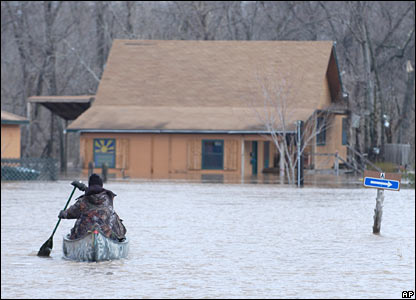 Man paddles boat in flooded street near Joplin, Missouri