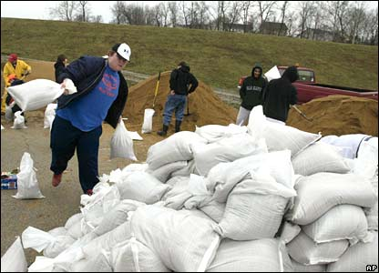 Joe Kiefer, a member of the Valley Park high school baseball team, throws sandbags onto a pile near the levee, built to hold back floodwaters in Valley Park, Missouri