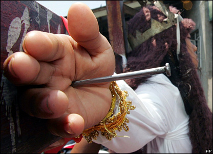 A nail penetrates the palm of Gwendelyn Pedrosa during a re-enactment of the crucifixion in Paombong, north of Manila, in the Philippines.