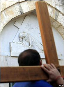 A Christian carries a cross along the Via Dolorosa in the old city of Jerusalem