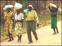 People carrying bags of maize seed