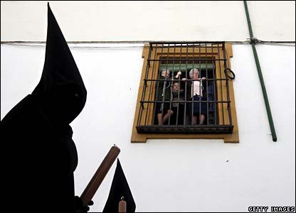 People look from a window at penitents of the Los Dolores brotherhood in Cordoba, Spain