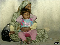 A Palestinian woman with her child rests outside a mosque on the edge of the Ain al-Hilweh refugee camp after fleeing her home, 21 March 2008