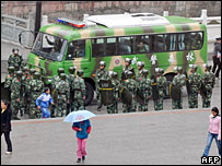 Tibetans walk past police in Kangding county, Sichuan province, 21 March 2008