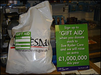 A pile of donated goods next to a Gift Aid sign