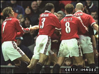 Manchester United players surround referee Andy D'Urso in 2000