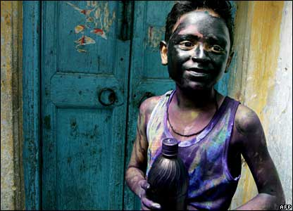A young Hindu boy looks on after being covered in colours during Holi celebrations in Dhaka, Bangladesh