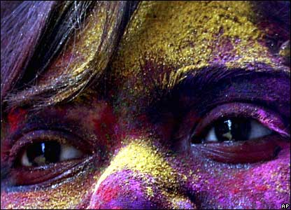 A girl with her face covered with coloured powder celebrates Holi in Calcutta, India