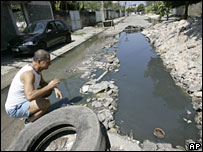 A man looks at stagnant water in the Curicica slum in Rio de Janeiro, 21 March 2008