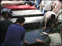 Iraqis mourn lost relatives after a stray rocket struck a residential building in Kamaliya, east Baghdad, on Sunday