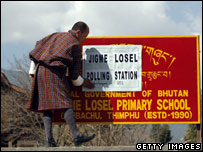 A man fixes the polling station sign at a school in Thimphu, Bhutan