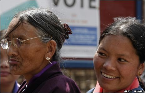 An old woman and young woman in a voting queue