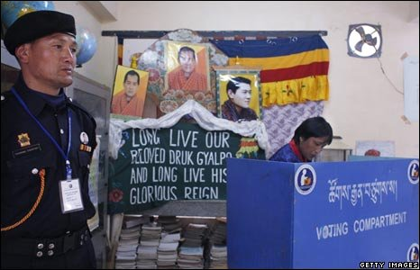 A man casts his vote with a  portrait of the king behind him