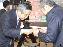 Japanese businessmen bow while exchanging namecards