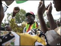 Zimbabwe's President Robert Mugabe greets party supporters upon his arrival in Mahusekwa