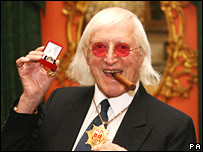 Sir Jimmy Savile with his commemorative badge at Downing Street