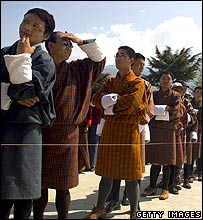 Bhutanese men queue at a polling station