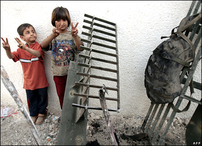 Iraqi children beside a bombed US military vehicle in Sadr City on 26 March 2008