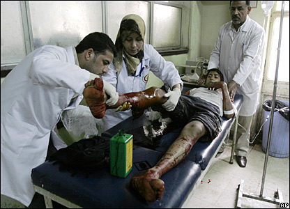 Medics help a wounded youth in Baghdad's Sadr City on 26 March 2008