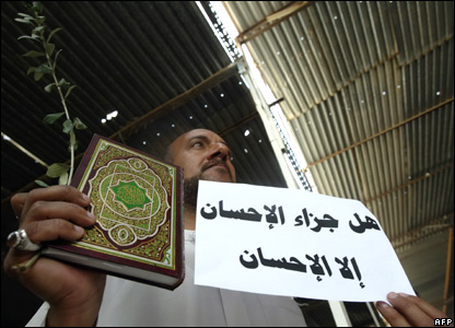 A Sadrist with a Koran and an olive branch in Karbala on 26 March 2008