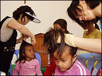 Korean missionaries treating Cambodian children for lice
