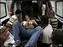 Medics help a man wounded in clashes between Mehdi Army and the Iraqi government forces Baghdad's Sadr City.