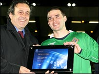 David Healy receives the award from Michel Platini at Windsor Park