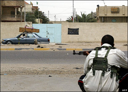 A Mehdi Army militiaman takes a combat position as a car carrying a coffin passes by during clashes in the southern Iraqi city of Basra.