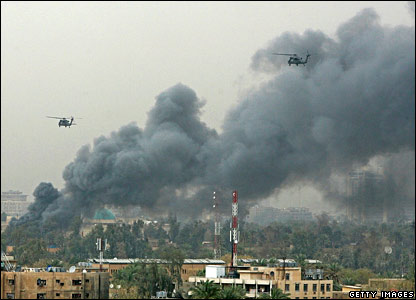 A helicopter flies past a column of smoke coming out of the heavily fortified Green Zone.