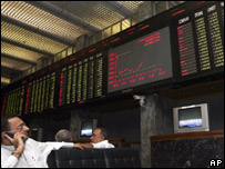 A Pakistani stock broker stands before a panel at Karachi Stock Exchange