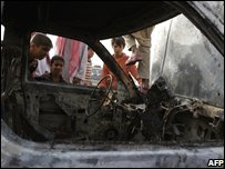 Children look at a burnt car in Karbala, Iraq
