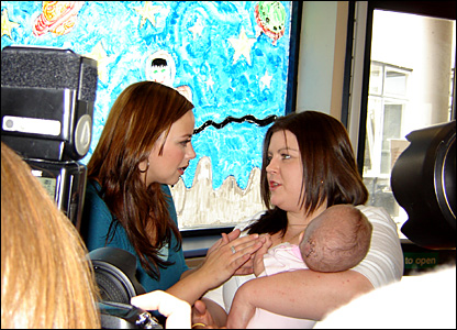 Photographers watch as Natasha Hardacre and baby Lacey Faulkner meet the singer.