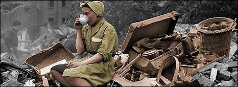 Woman sits on bomb rubble drinking a cup of tea.