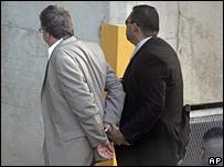 Un oficial del FBI lleva esposado a uno de los acusados