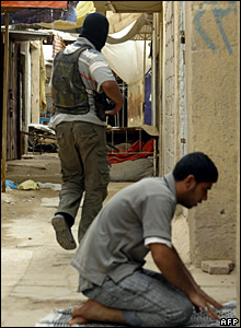 A Shia fighter runs for cover as a man performs prayers in Basra, 28 March 2008