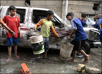 Children use buckets to remove water after water pipes were hit in shelling in Baghdad, 28 March 2008